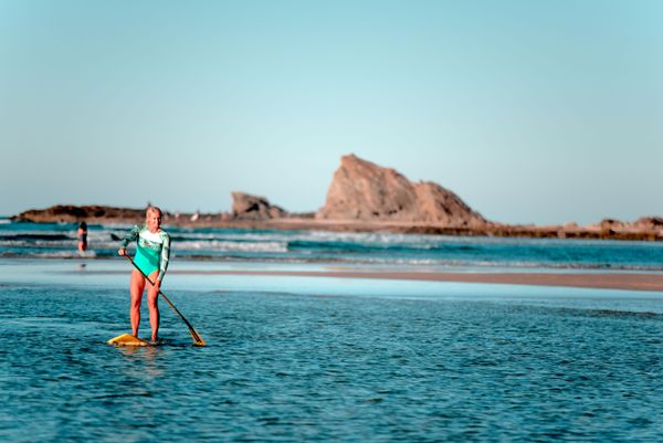 Girl standing on paddleboard preparing for ocean swimming,with mountains in the background